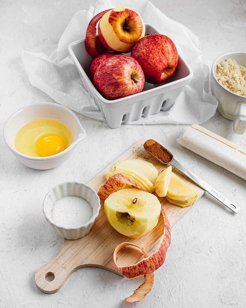 Apple ingredients with egg, sliced apples, sugar and spices