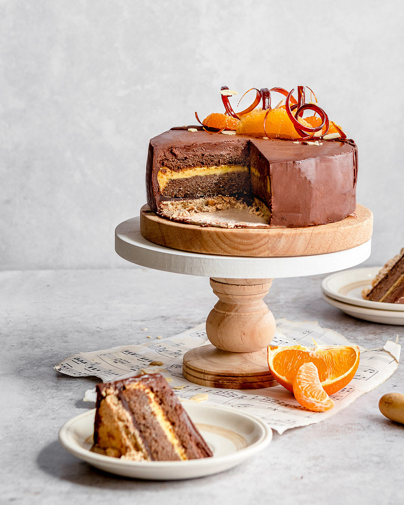 slicing into a citrus chocolate layer cake