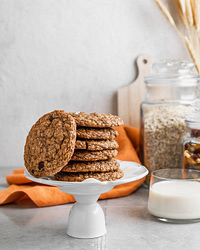 A large stack of crispy oatmeal date cookies