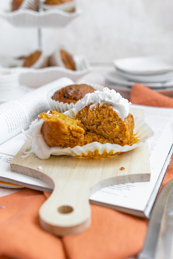 carrot cake muffins with coconut frosting cut in half on a tray