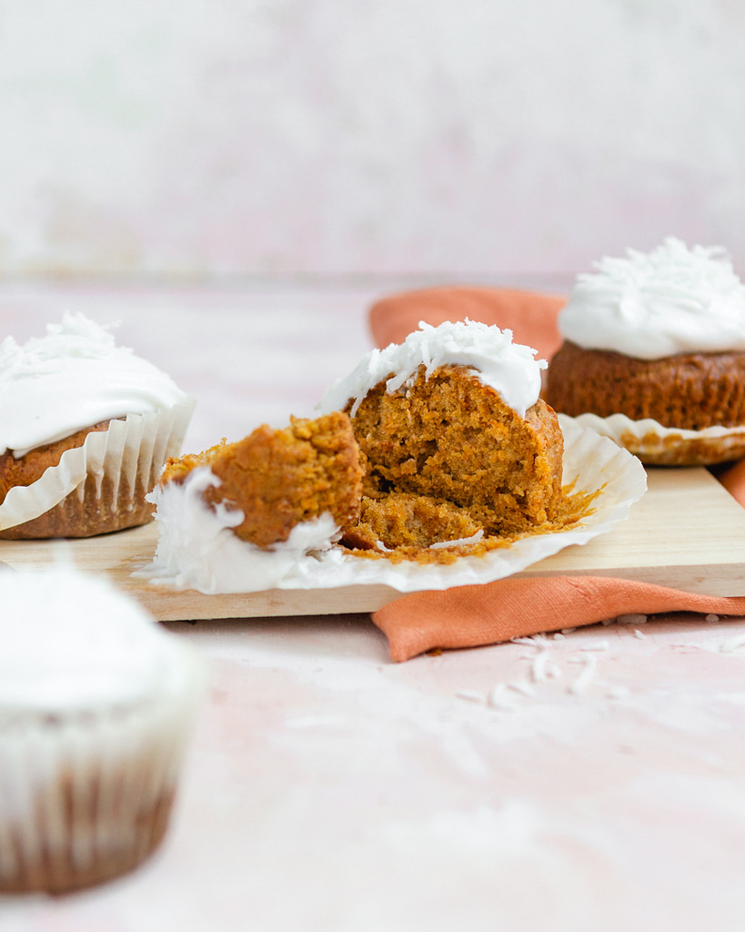 a cutting board with carrot cake muffins