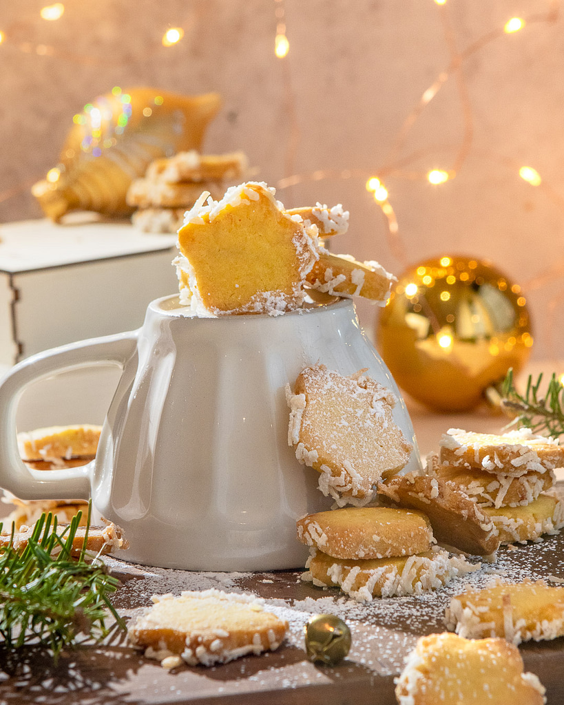 Star butter cookies stacked on a mug with golden christmas decorations