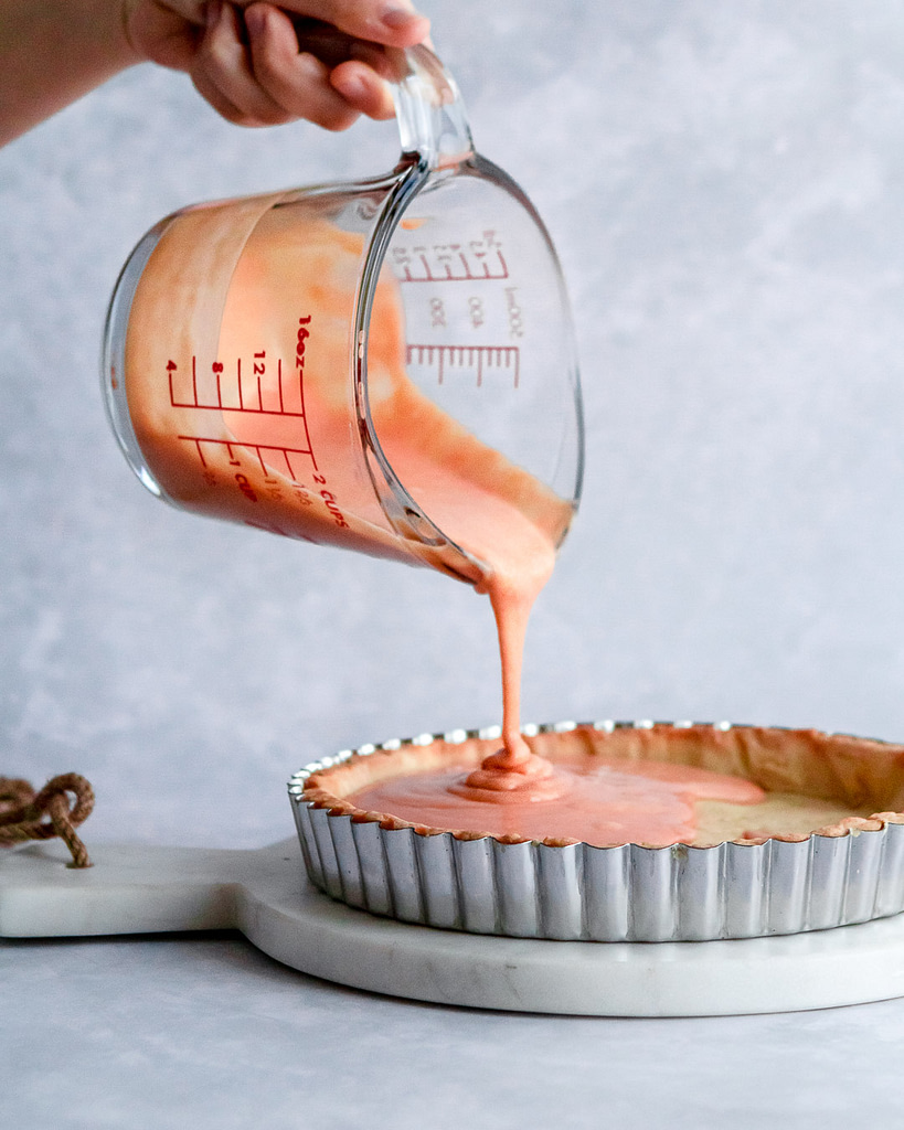 pouring orange curd into a baked tart