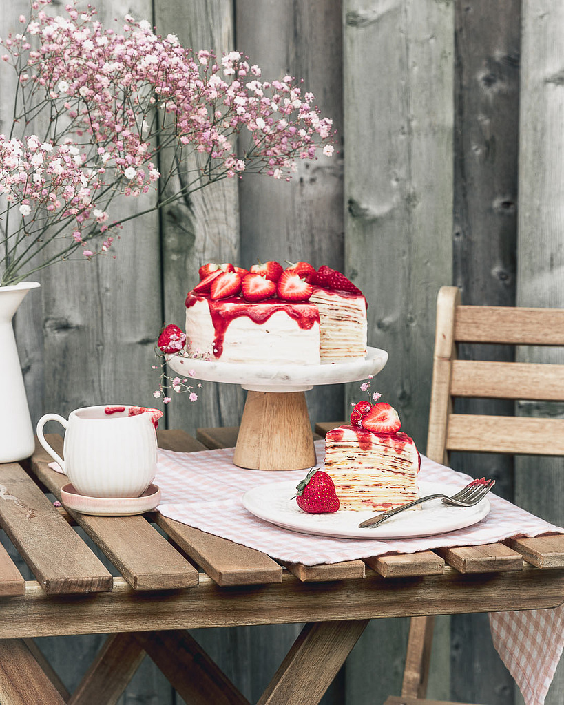 a strawberry vanilla crepe cake with a slice on a plate