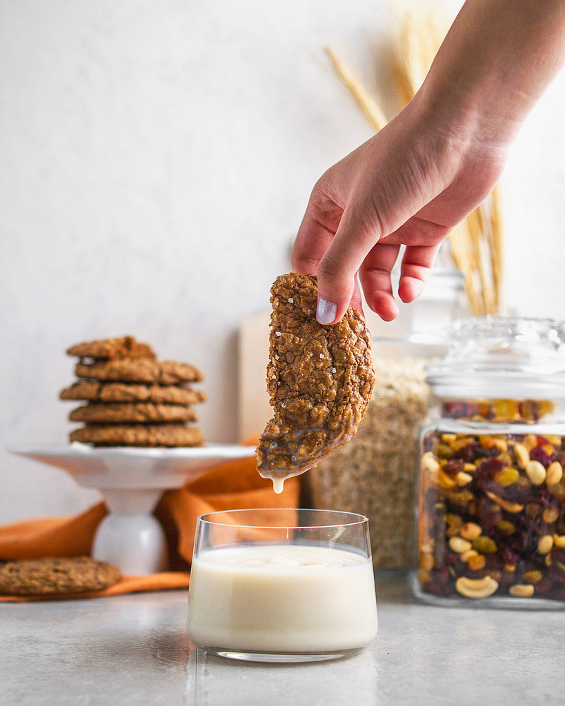 A hand dipping half a crispy oatmeal date cookie into a glass of milk