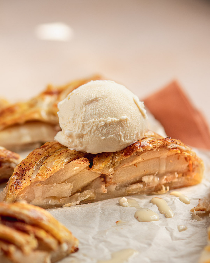 A slice of Apple strudel with vanilla ice cream dripping down on top
