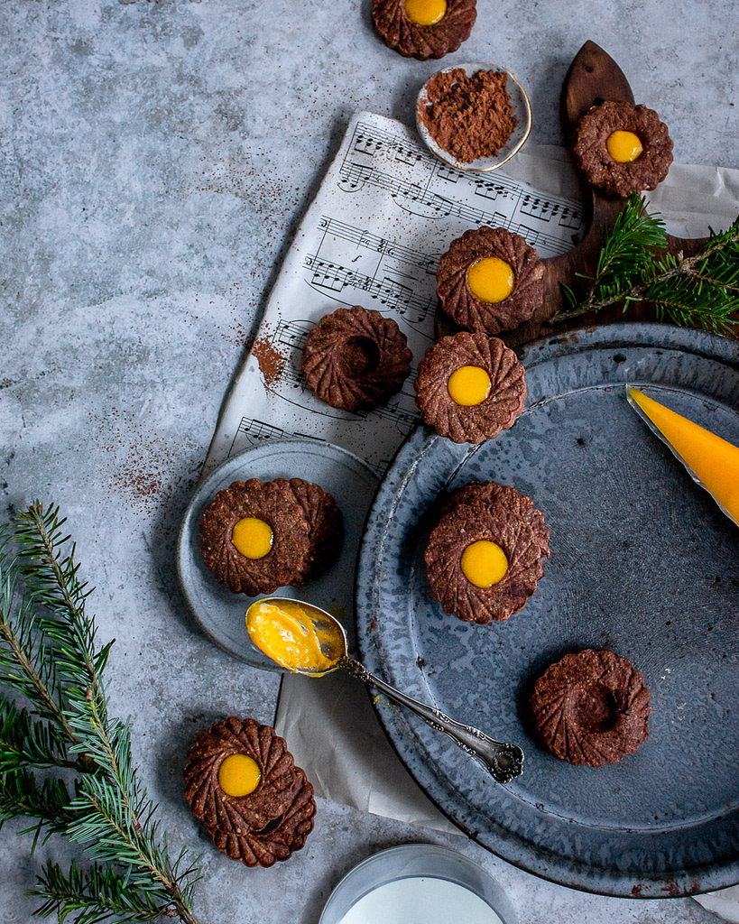 Chocolate lemon curd linzer cookies on a blue baking tray