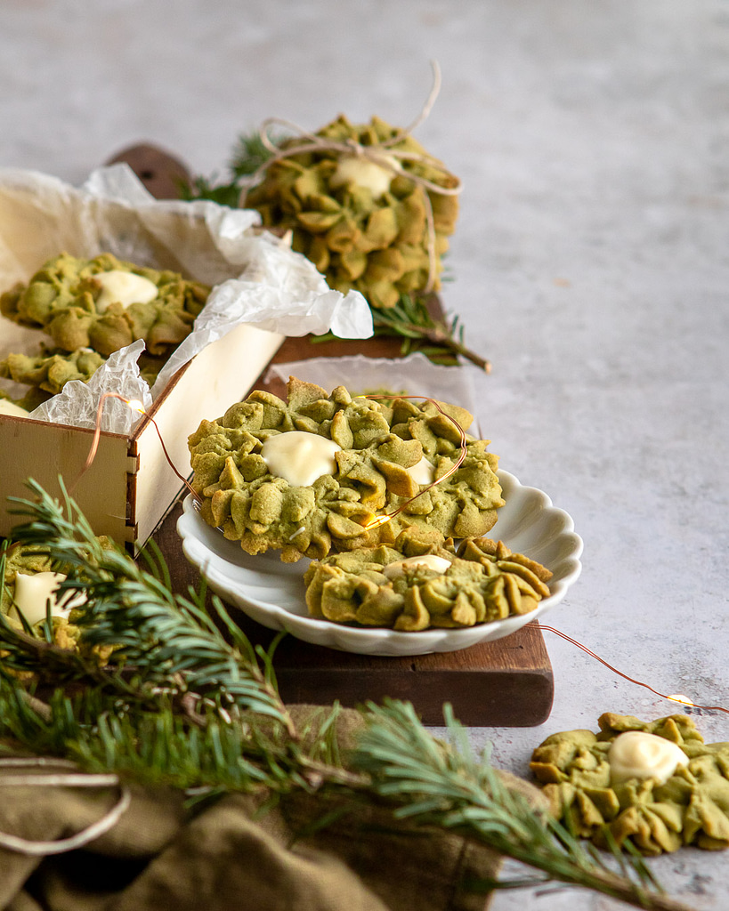 Matcha White chocolate wreath cookies surrounded by fairy lights and on a white scalloped dish