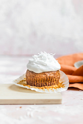 a carrot cake muffin topped with coconut frosting and coconut shreds