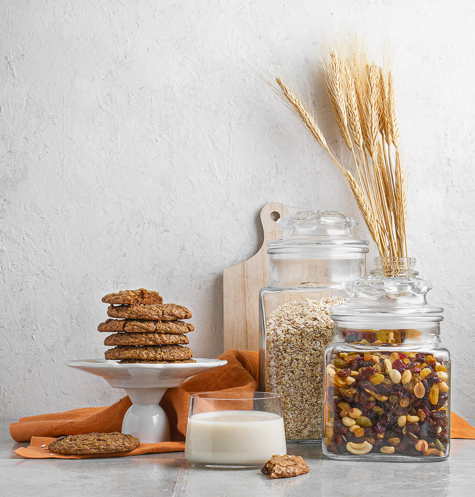 Jars of dates, oatmeal, milk and a stack of cookies on a plate