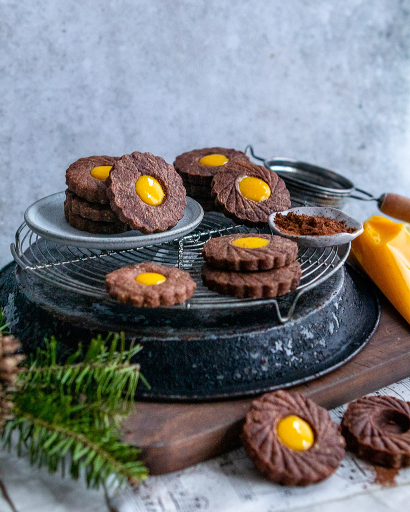 chocolate lemon curd linzer cookies stacked on a cooling rack