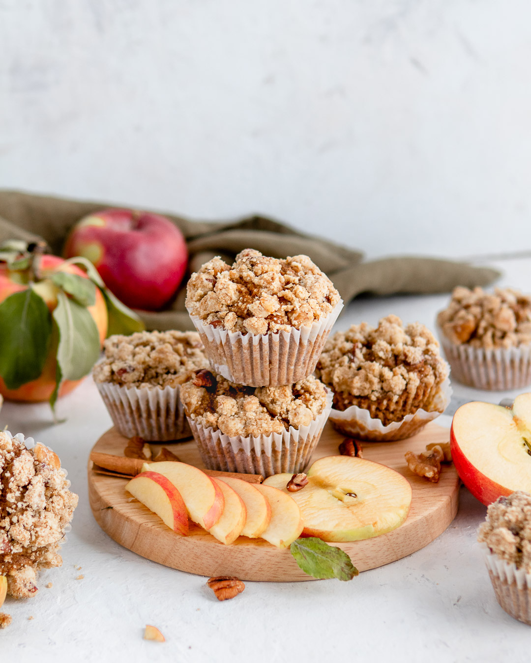 Stacked muffins on a cutting board with sliced apples