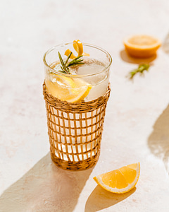 A rattan glass filled with Sparkling Rosemary Ginger Lemonade