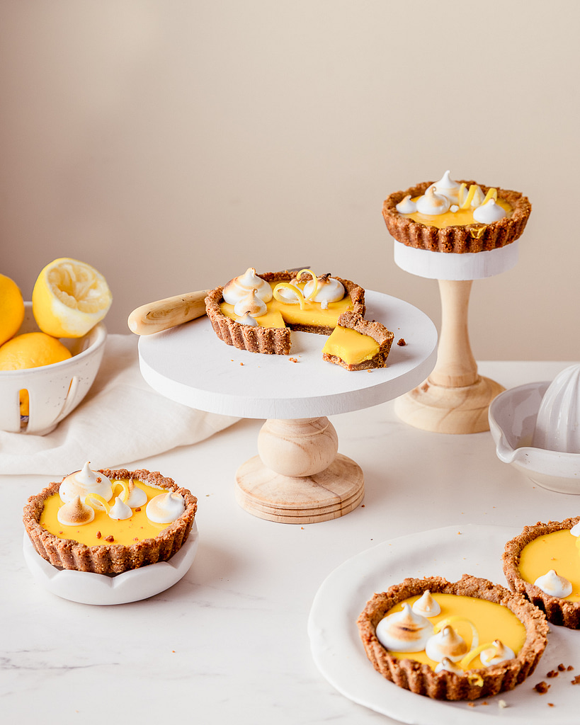 lemon tarts with a bite taken out of a slice